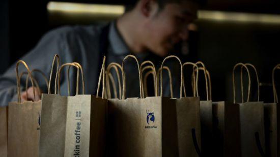 Employee behind Luckin Coffee paper bags