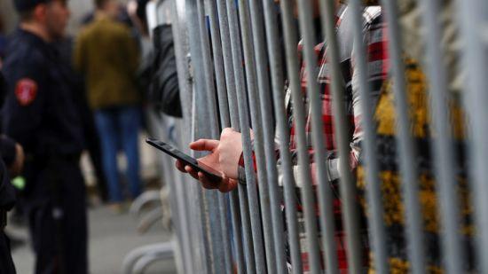 hands holding phone through railings
