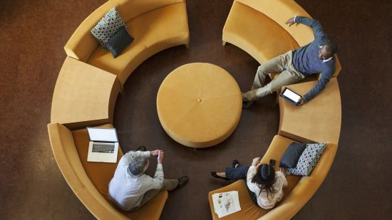 Overhead view of people sitting on a circular sofa, surrounded by devices
