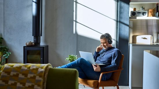 Man siting in armchair looking at laptop with headphones on