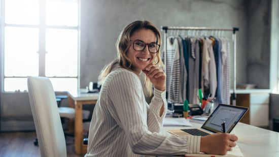 Smiling woman on a laptop at a desk