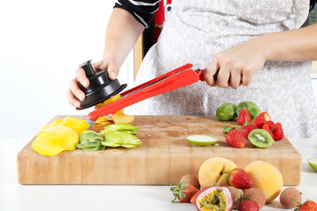 Slicing fruit for the fruit salad by using a mandoline