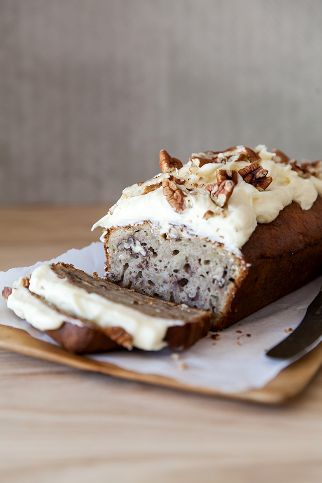 Banana bread with cream cheese icing and pecan nuts