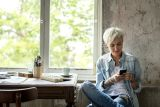 Woman with short white hair sat at home looking on mobile to buy the morning after pill online