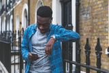 Young black man standing on quiet street in London using his phone to research photo assessment online
