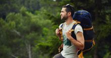 Man hiking in the forest glad that he has purchased malaria tablets for this holiday