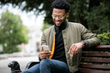 Happy young black man sat on park bench smiling at phone because he has found a way to order erectile dysfunction treatment online