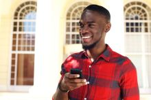 Black man smiling whilst searching on his mobile phone for premature ejaculation treatment