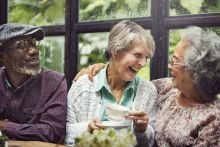Elderly friends at a cafe smiling and laughing because they are managing their high cholesterol with statins