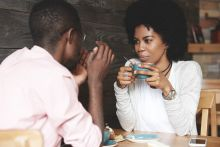 Black couple sat at cafe discussing how to quit smoking