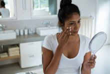 Indian woman is looking at her face in a hand mirror for signs that her acne treatment is working