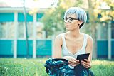 Young woman with blue short hair sat outside using her tablet to research bacterial vaginosis treatment