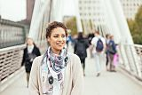 Young black woman standing on millennium bridge smiling because she's found genital herpes treatment