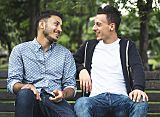 Two young men sat on a park bench smiling and discussing treatment for genital warts