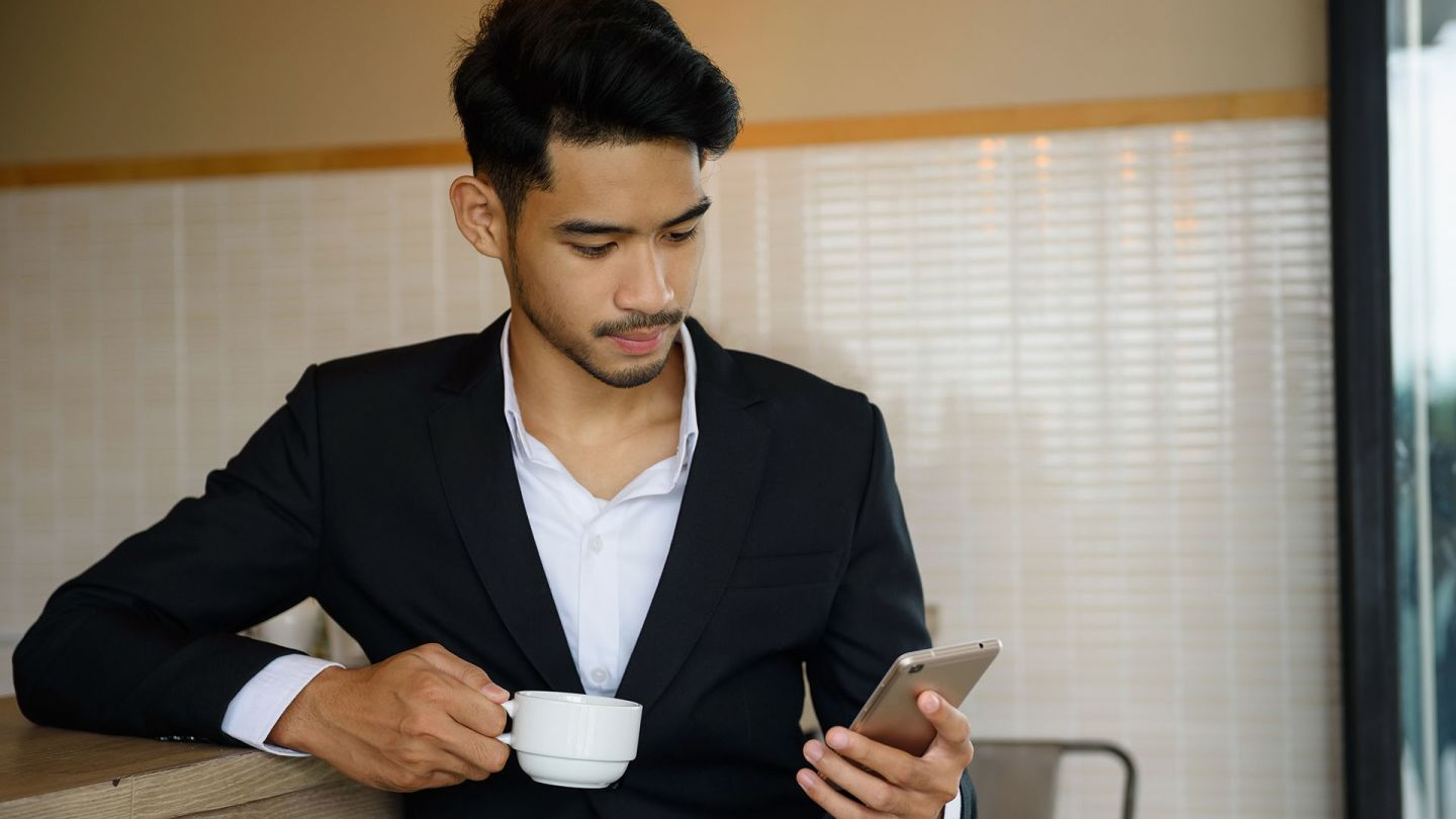 Man in a cafe holding an espresso looking for male enhancement pills on his phone
