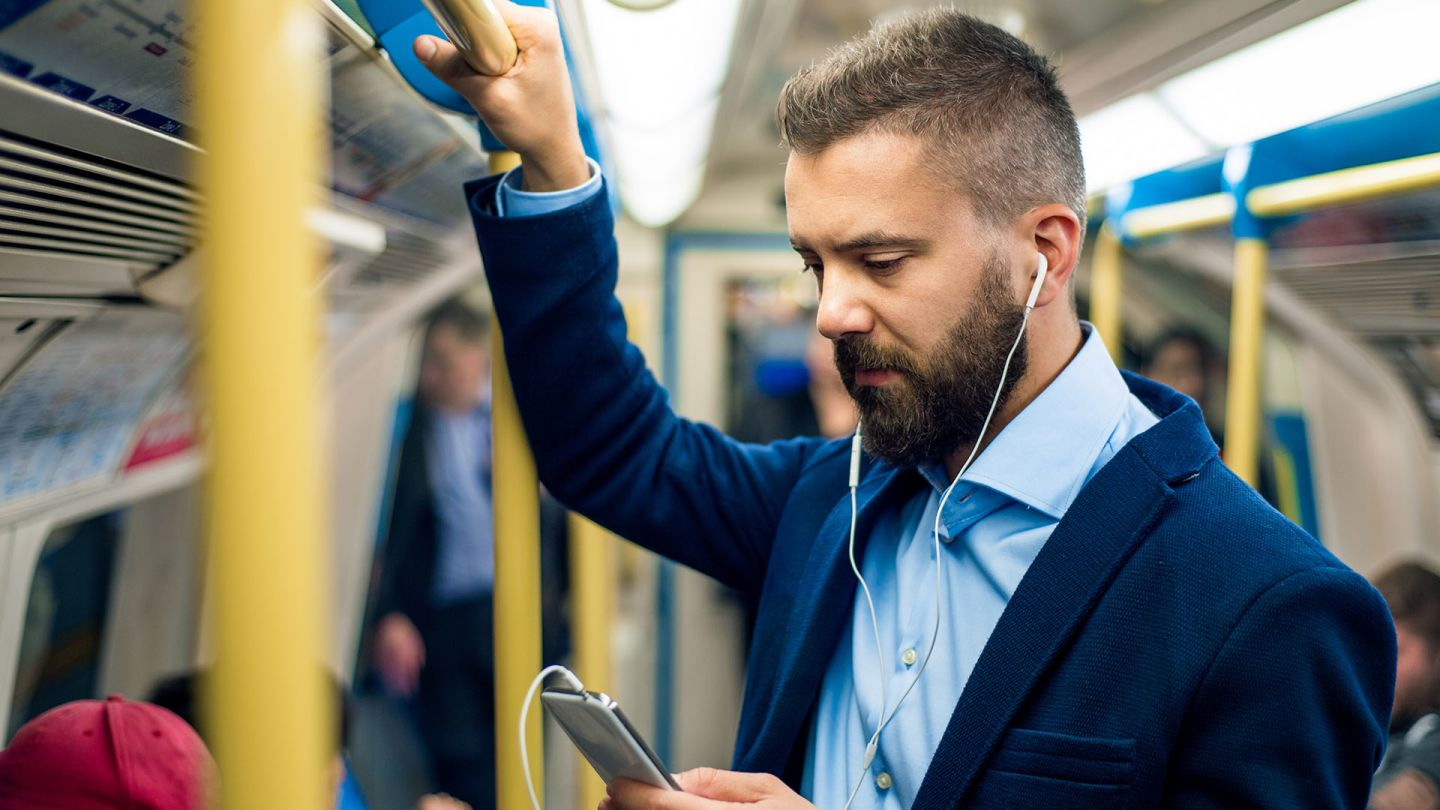 Man on the tube checking how long Viagra lasts on his smartphone