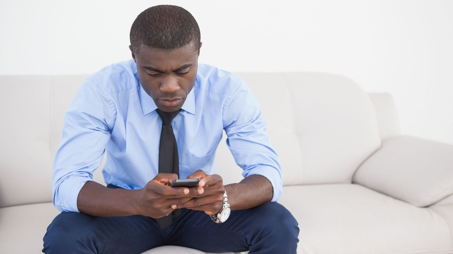 Man sat on a sofa looking up what Kamagra is on his phone