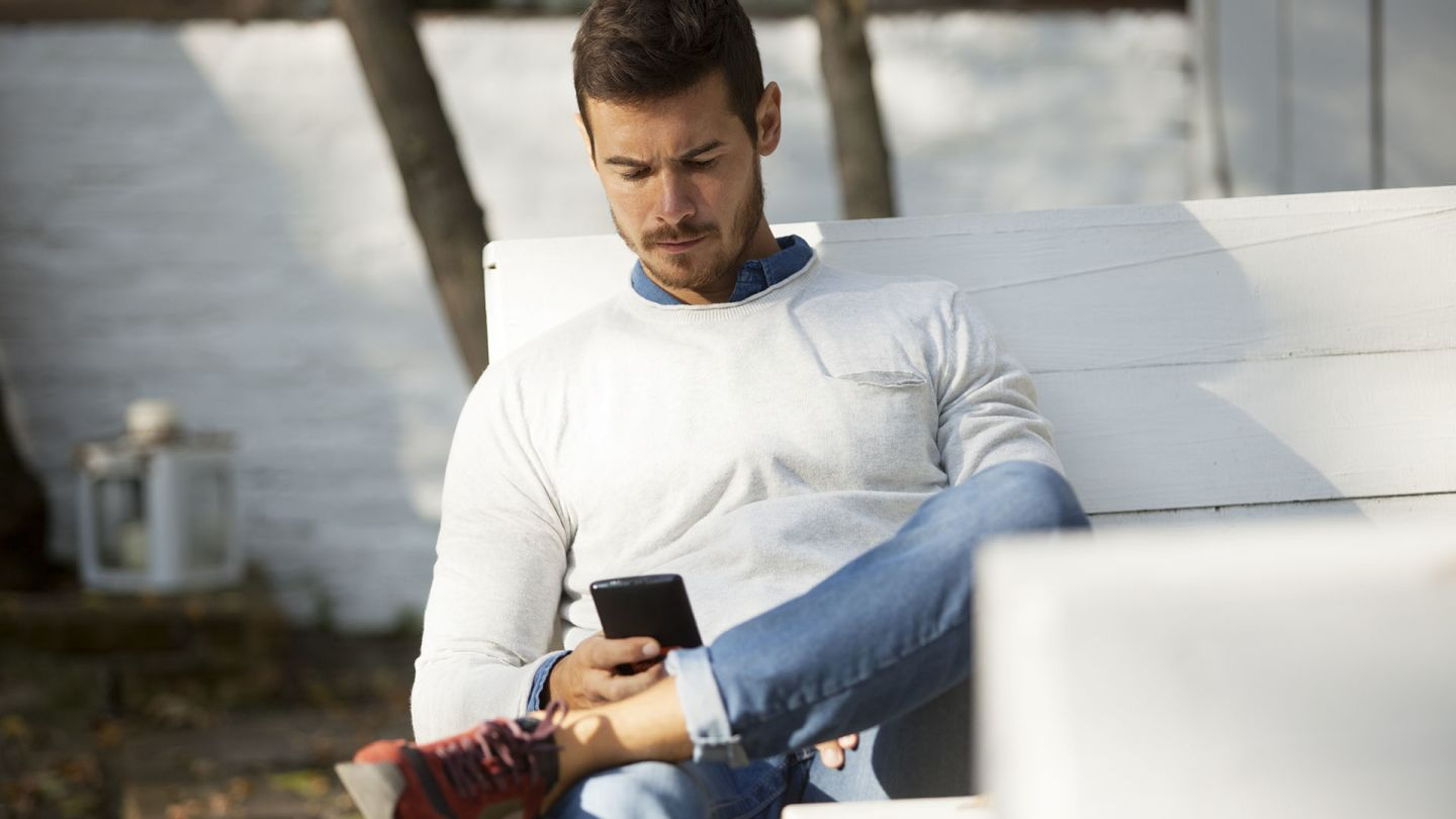 Man sat on a bench in his garden reading about Peyronie's disease on his phone