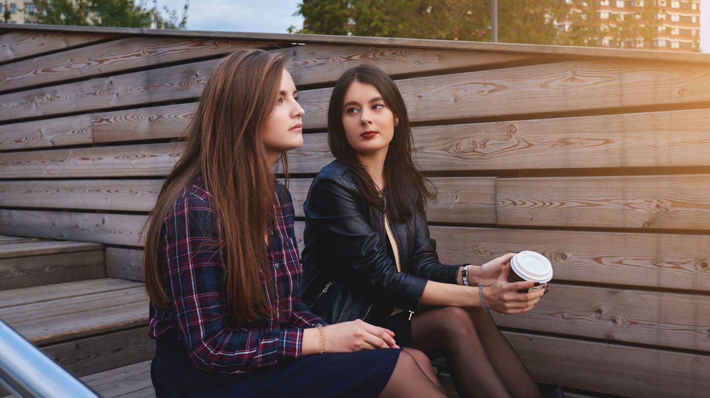 2 woman sat on wooden steps talking about pelvic inflammatory disease