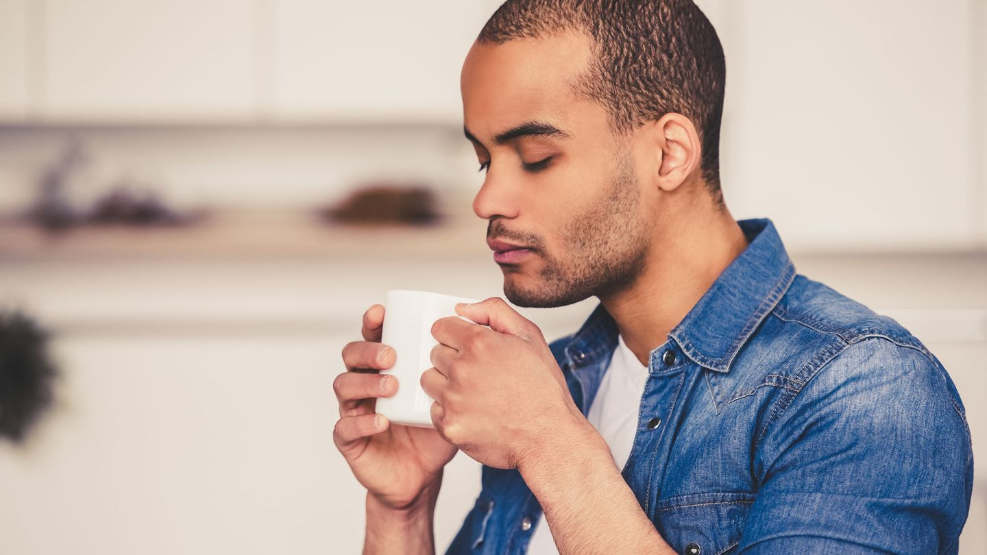Man leaning over a mug of tea wondering if there are natural cures for erectile dysfunction