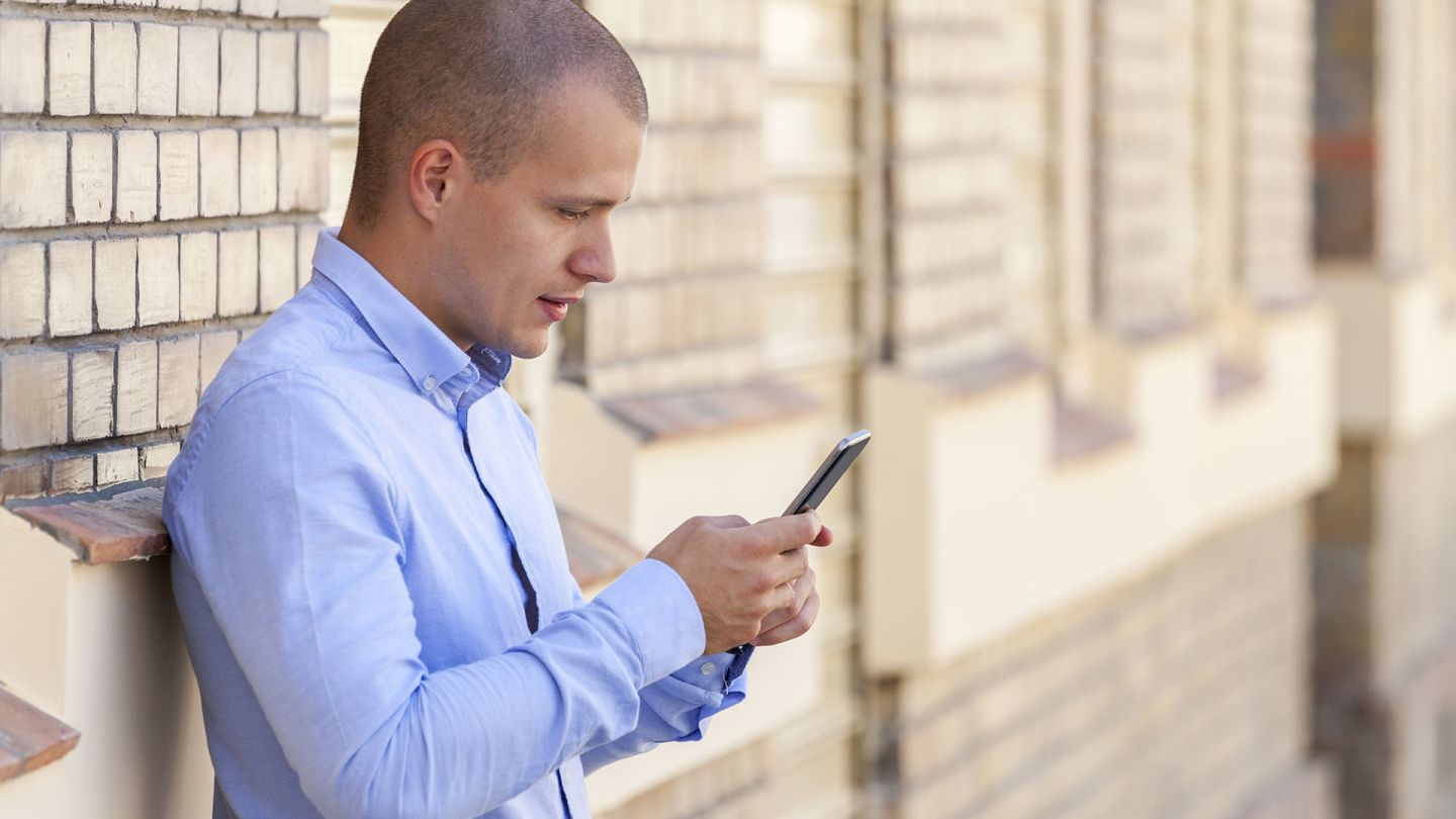 Man outside building typing on mobile phone to see a list of STDs