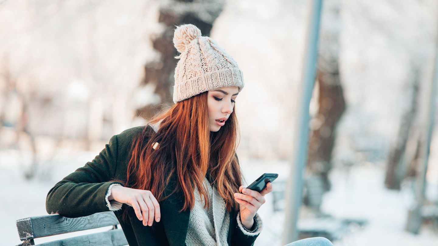 Woman sat on a park bench in the snow is checking her phone for information about contraceptive injections