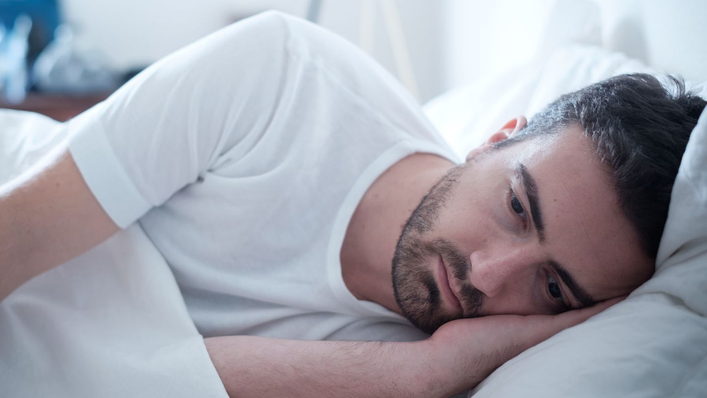 Man lying in bed on side looking worried because he might have hiv rash
