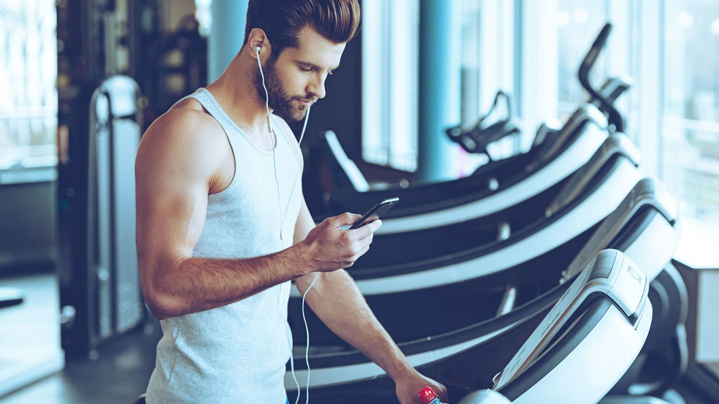 Man at the gym who has stopped using the treadmill looking up exercise induced asthma on his phone