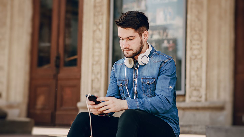 Man sat on steps outside shop looking up erythomycin tablets on his phone