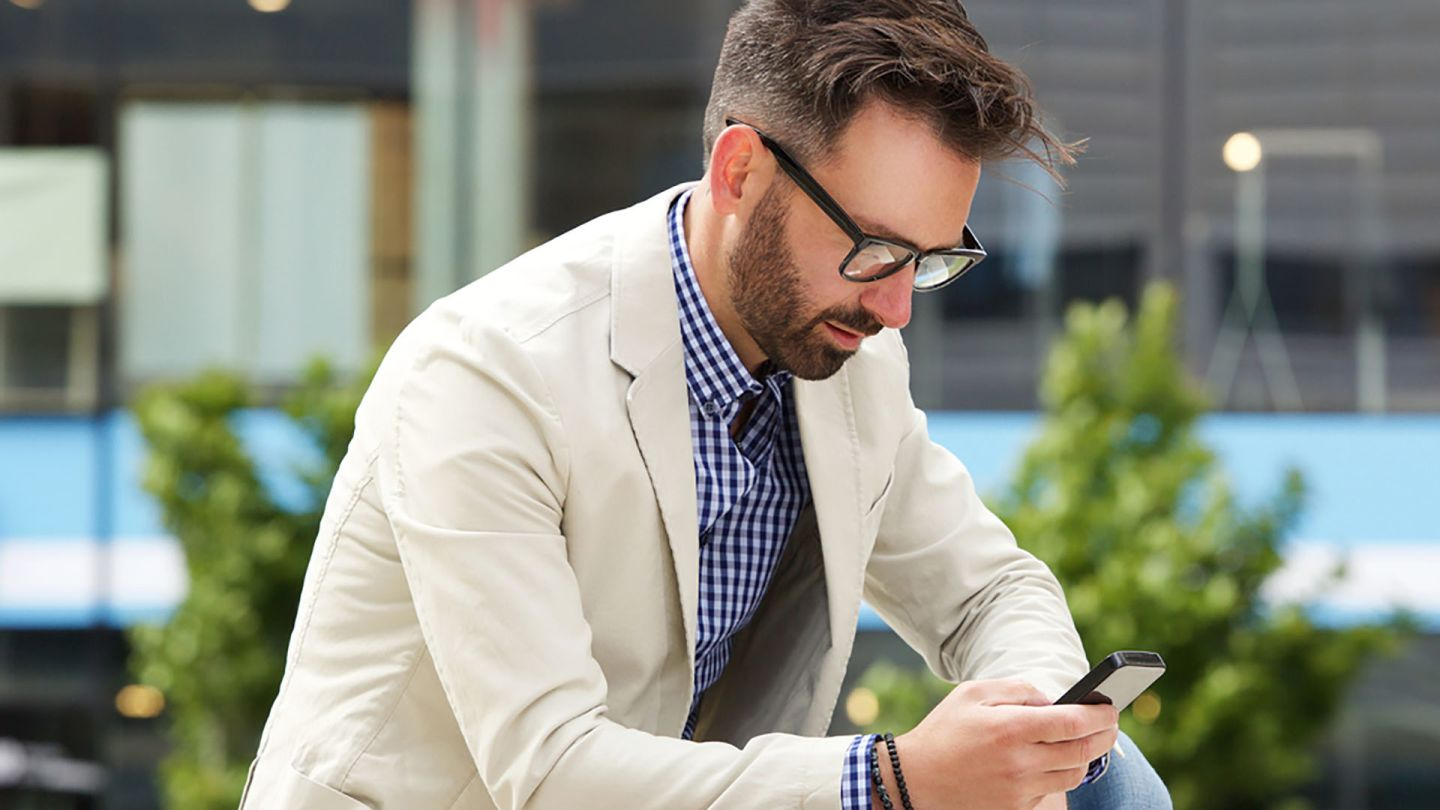 Man wearing glasses sat outside looking up early symptoms of hiv on mobile phone