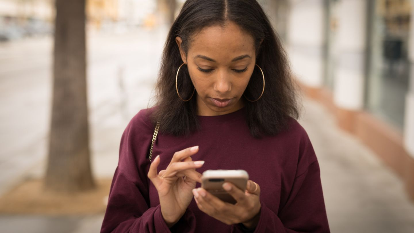 Black girl walking down street scrolling on mobile to find information on morning after pill side effects