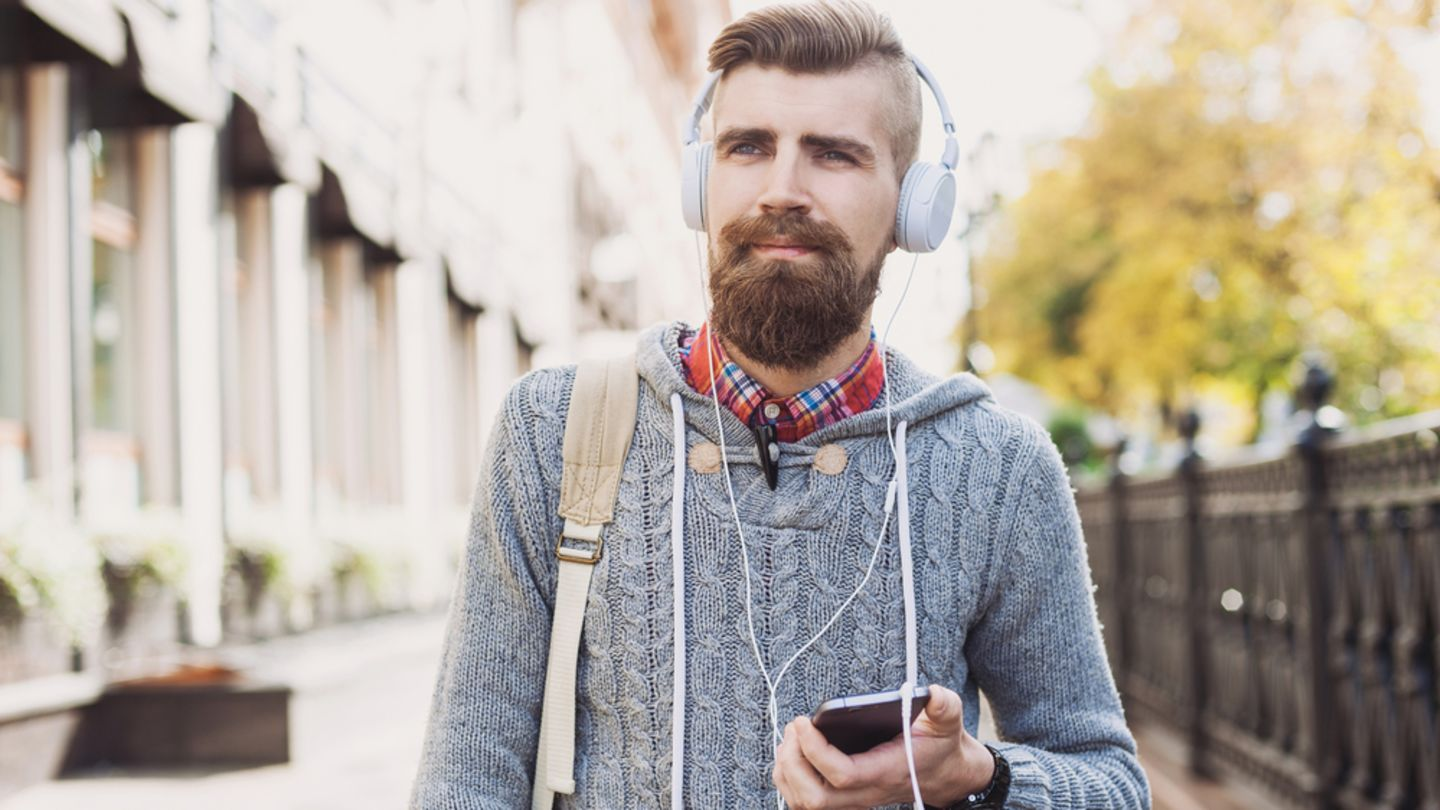 Bearded man walking with phone in hand thinking about what the symptoms of hiv in men are