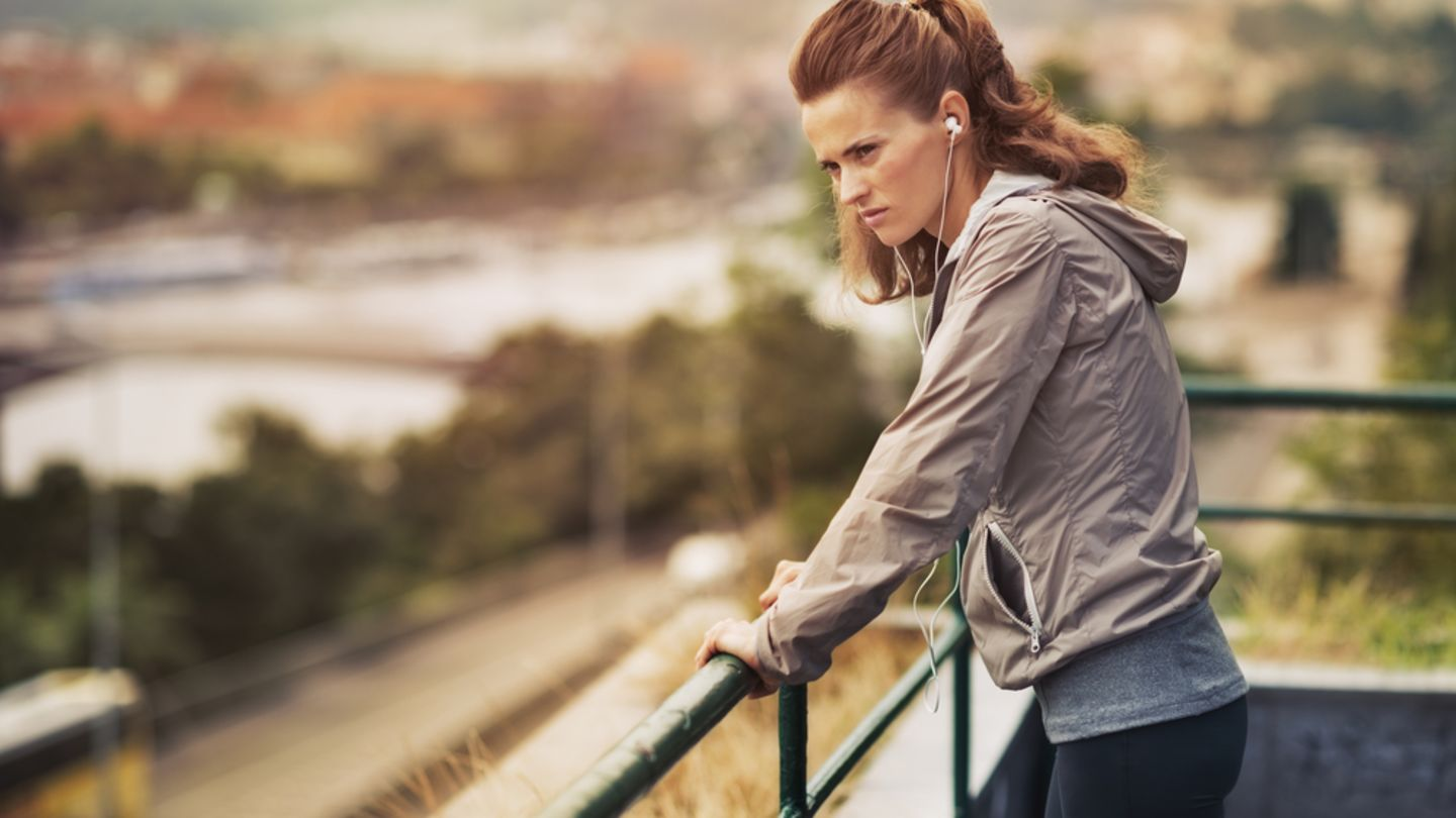 Woman who has stopped jogging leaning on railings wondering if jogging causes low blood pressure