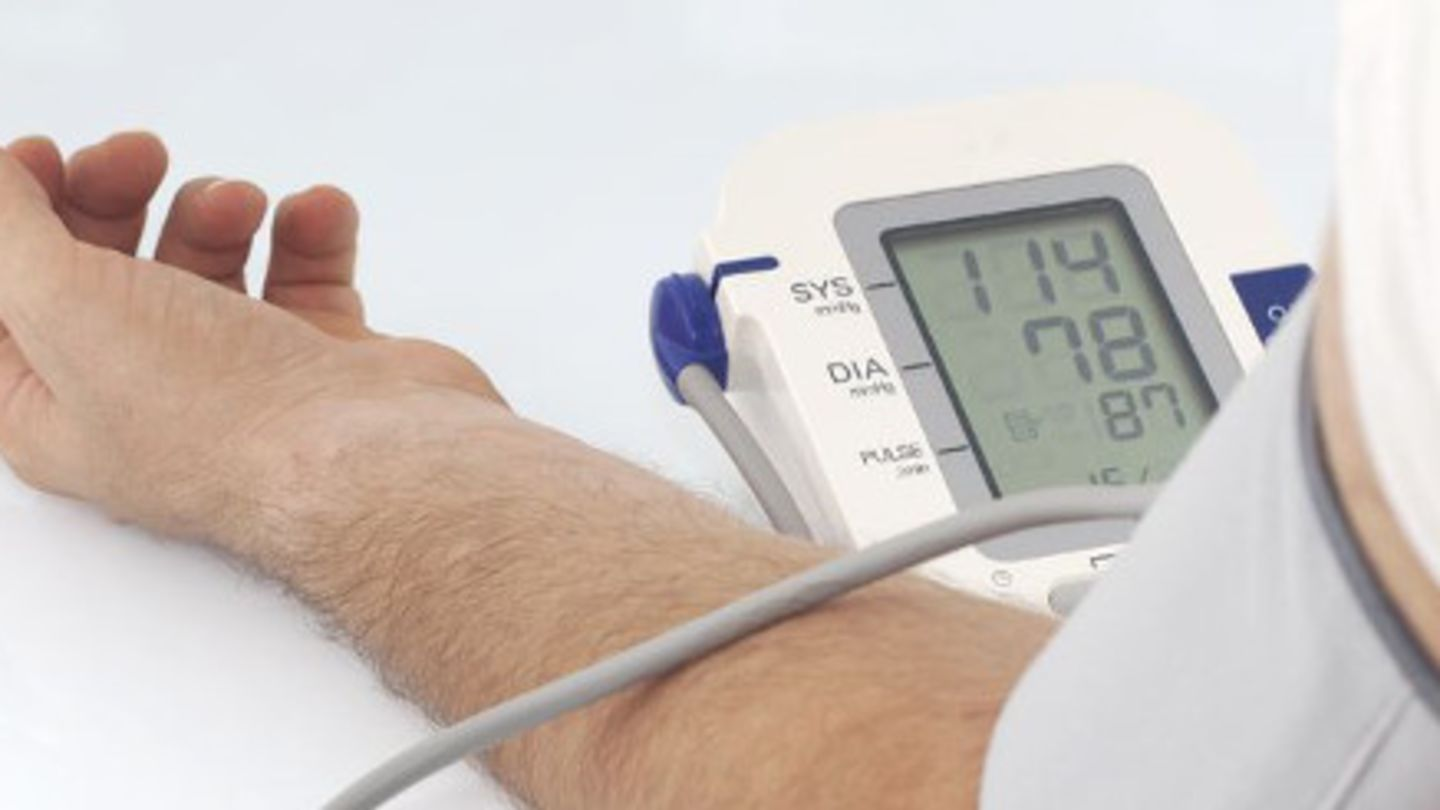 Man with his arm strapped to a monitor that shows high blood pressure is in need of treatment for hypertension
