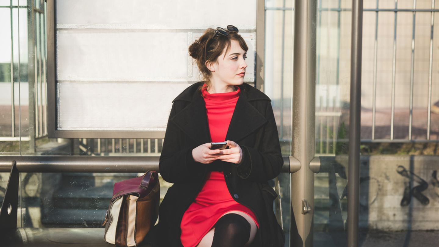 Woman sat at a bus stop is checking on her phone for the symptoms of chlamydia in women