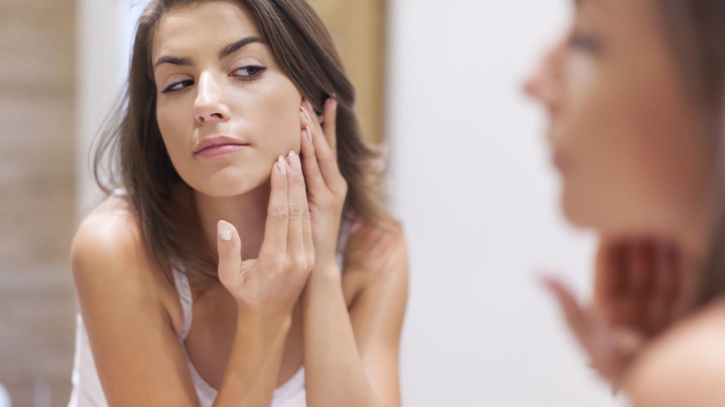Woman looking in a bathroom mirror checking her face for signs on acne