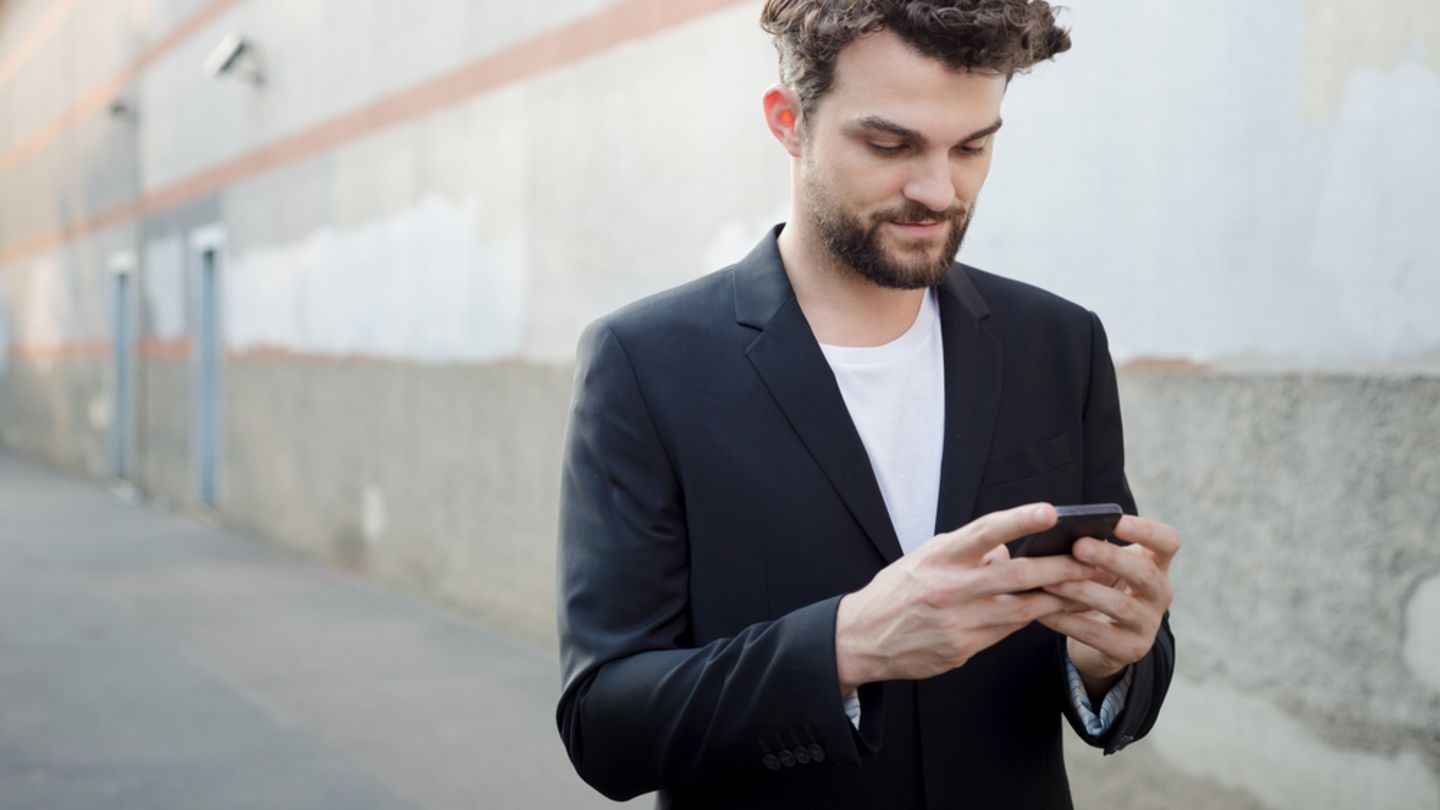 Man looking on his phone for erection pills as he walks down a concrete street