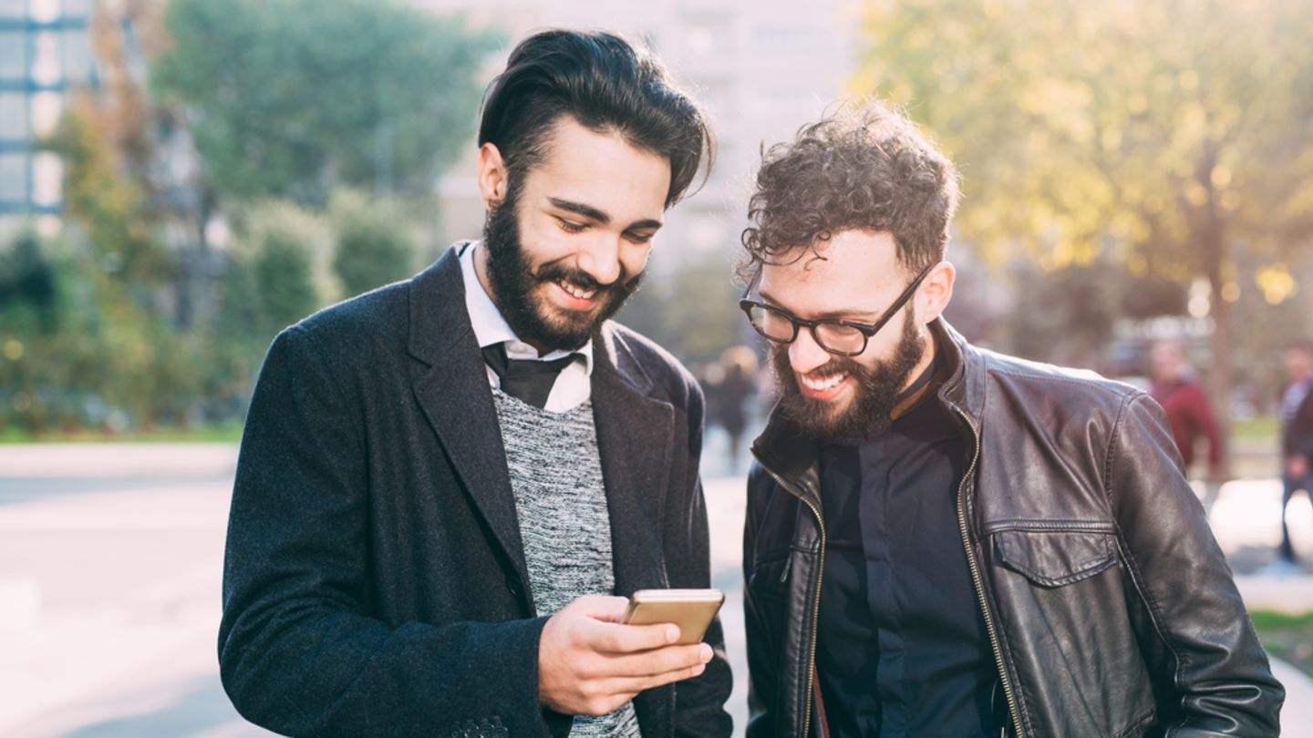 2 men reading about buying prescription drugs online together on one phone