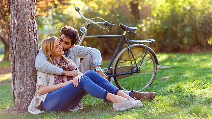 Mixed-race junger Mann mit Laptop sitzen unter Bäumen, dating website Profil - Stockfoto.