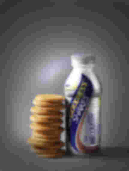 bottle of goodness shakes sports drink next to a stack of 15 ginger nut biscuits