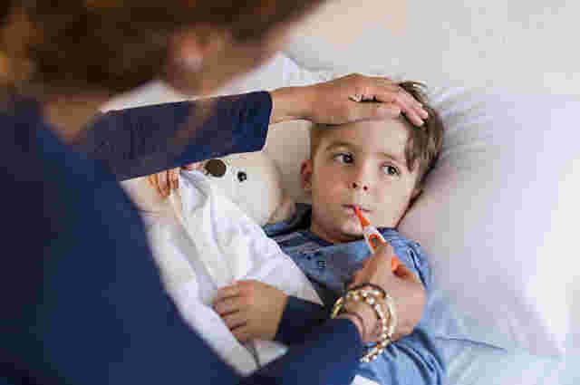 Frau hält den Kopf und misst Fieber ihres Kindes