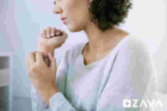 Junge Frau kratzt an einem, durch eine Kälteallergie ausgelösten, allergischen Ausschlag am Handgelenk.