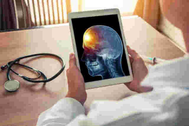 Arzt schaut auf ein Tablet, auf dem das Röntgenbild eines Kopfes zu sehen ist