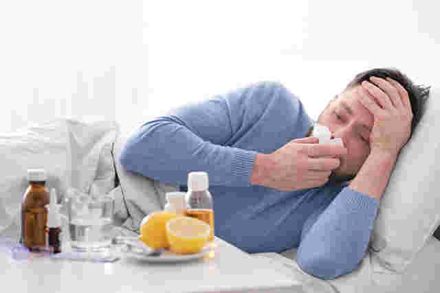 Mann liegt krank im Bett, vor ihm stehen Medikamente und Hausmittel, er putzt sich die Nase