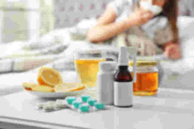Medikamente, Nasenspray, Honig, Tee und Orangen auf dem Tisch, Frau putzt sich im Hintergrund die Nase auf der Couch