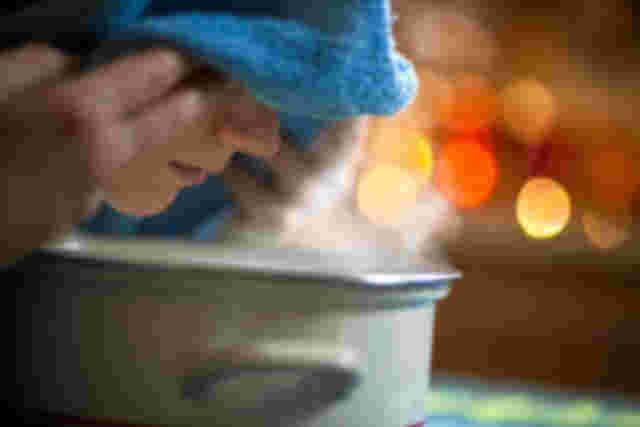 Frau atmet / inhaliert Dampf ein als Hausmittel