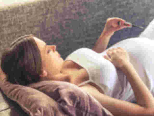 Schwangere liegt auf der Couch und misst Fieber