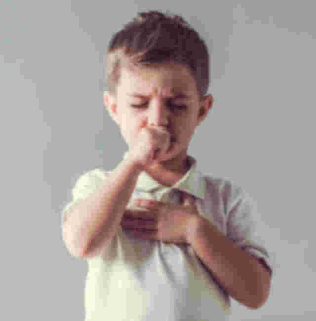 Kleiner Junge hält sich die Hand vor den Brustkorb und hustet in Faust