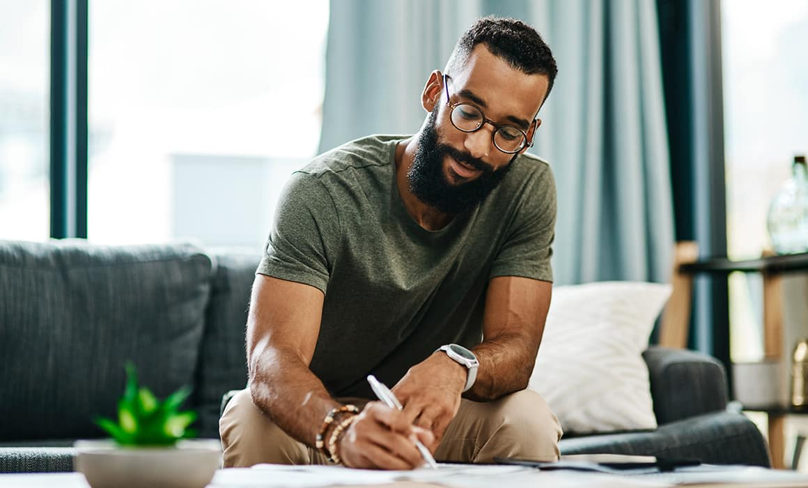 young man with beard writing in a journal.