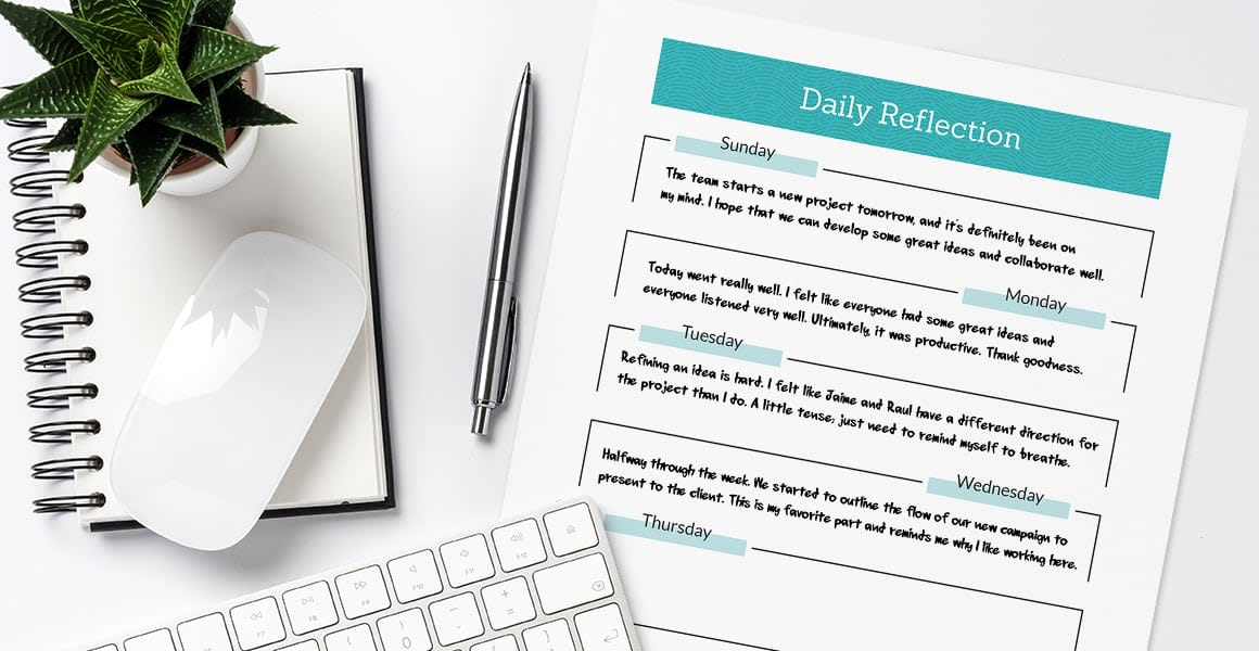 daily reflections paper next to journal, plant, and pen.
